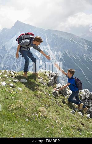 Teenage boys helping friend climbing in mountains - Stock Photo