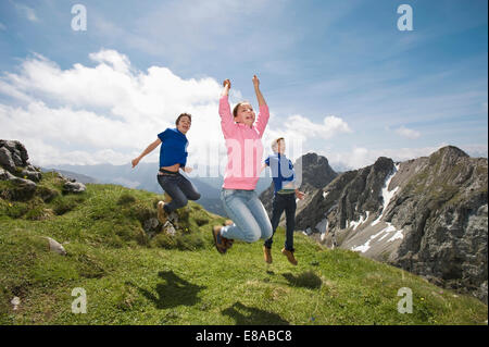 Girl and teenage boys jumping in air Alps - Stock Photo