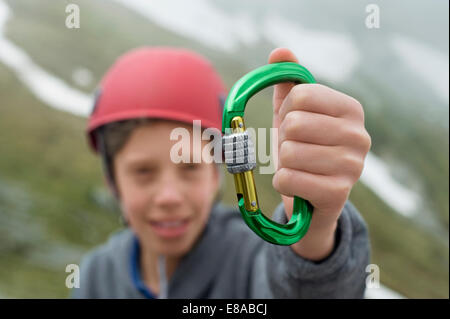 Young boy helmet holding climbing Carabiner - Stock Photo