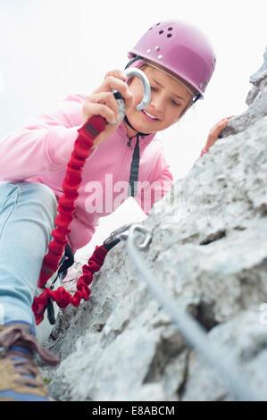 Young girl climbing attaching carabiner to rope - Stock Photo