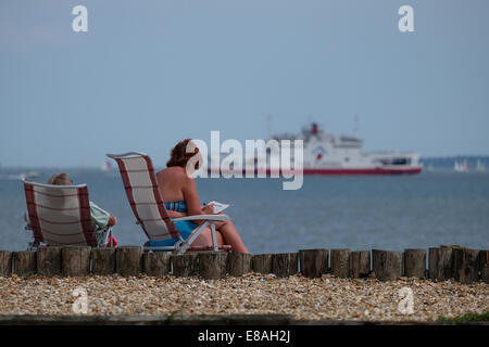 A couple relaxes on Calshot beach looking out to the Solent as a red Funnel boat goes to the isle of Wight - Stock Photo