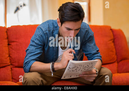 Young man sitting doing a crossword puzzle looking thoughtfully at a magazine with his pencil to his mouth as he - Stock Photo
