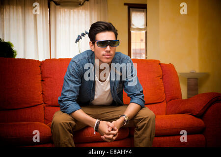 Young man in 3d glasses sitting on a sofa in the living room watching reality television leaning forwards with an - Stock Photo