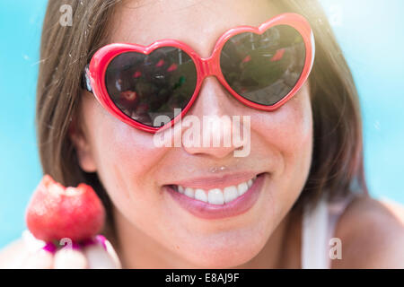 Close up portrait of young woman eating strawberry - Stock Photo