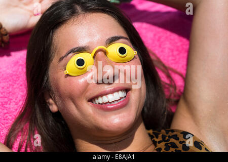 Portrait of young woman sunbathing, wearing goggles - Stock Photo