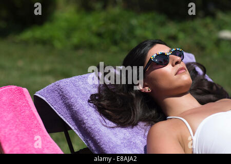 Young woman sunbathing on lounger in garden - Stock Photo