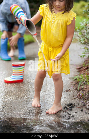 Girl pouring water from rubber boots into rain puddle - Stock Photo
