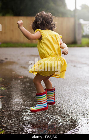 Girl wearing rubber boots jumping in rain puddle - Stock Photo