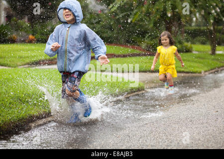 Boy and sister wearing rubber boots running and splashing in rain puddle - Stock Photo