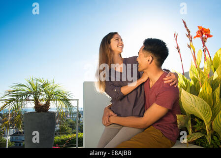 Couple with arms around each other in penthouse rooftop garden, La Jolla, California, USA - Stock Photo
