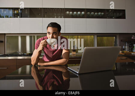 Young man in dining room drinking coffee - Stock Photo