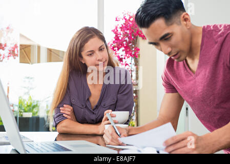 Worried couple checking bills and paperwork in dining room - Stock Photo