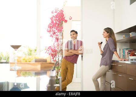 Couple chatting and drinking wine in dining room - Stock Photo