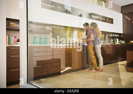 Loved up couple cooking on hob in kitchen - Stock Photo