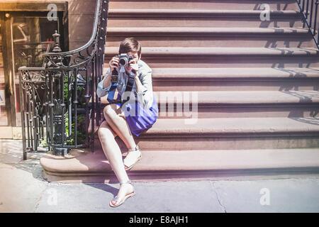 Photographer sitting on steps, New York, US - Stock Photo