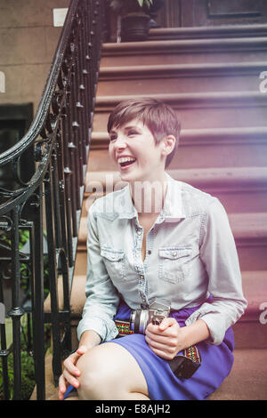 Young woman sitting on steps with camera, New York, US - Stock Photo