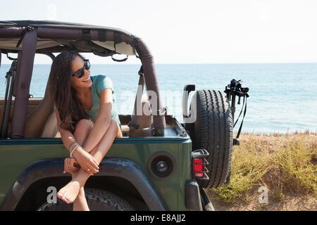 Young woman sitting in jeep window, Malibu, California, USA - Stock Photo