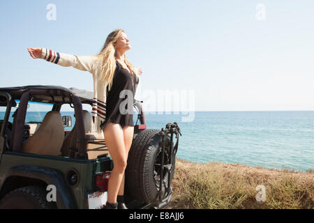 Young woman standing on back of jeep at coast with arms outstretched, Malibu, California, USA - Stock Photo