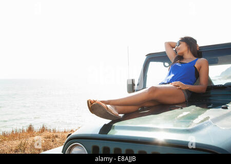 Young woman reclining on hood of jeep at coast, Malibu, California, USA - Stock Photo