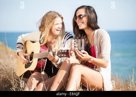 Two young women with acoustic guitar at coast, Malibu, California, USA - Stock Photo