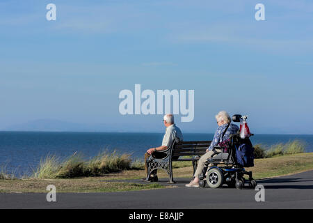 Man sitting on bench with wife in wheelchair on a coastal path in Blackpool, Lancashire, UK - Stock Photo