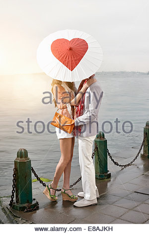 Romantic young couple behind heart umbrella with arms around each other on lakeside - Stock Photo
