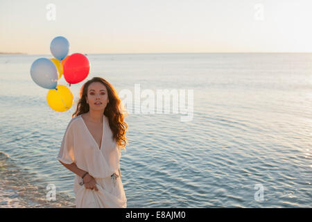 Portrait of young woman on beach with balloons, Castiadas, Sardinia, Italy - Stock Photo