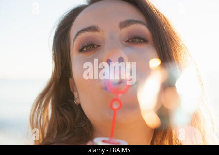 Close up of young woman blowing bubbles on beach, Castiadas, Sardinia, Italy - Stock Photo
