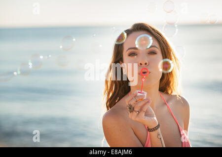 Portrait of young woman on beach blowing bubbles, Castiadas, Sardinia, Italy - Stock Photo