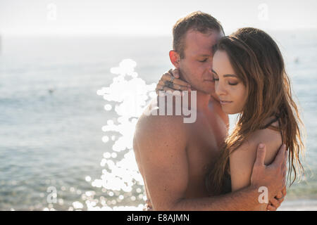Romantic young couple embracing on beach, Castiadas, Sardinia, Italy - Stock Photo