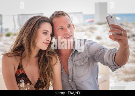 Young couple taking selfie on smartphone at beach, Castiadas, Sardinia, Italy - Stock Photo