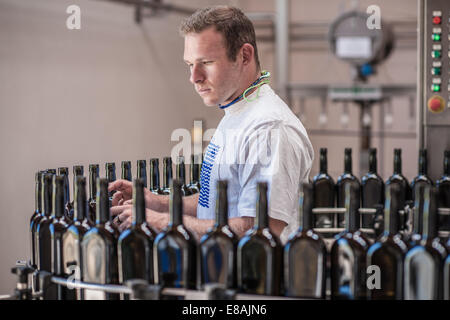 Young man working on production line in bottling plant - Stock Photo