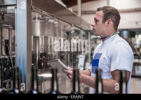 Young man working on production line with digital tablet in bottling plant - Stock Photo