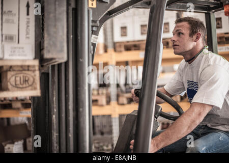 Young man driving forklift truck in factory warehouse - Stock Photo