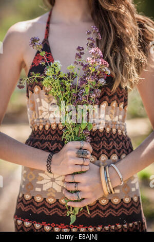 Cropped shot of young woman holding bunch of wildflowers - Stock Photo