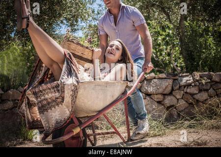 Young man pushing girlfriend in wheelbarrow, Castiadas, Sardinia, Italy