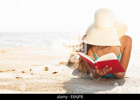 Young woman sunbathing and reading book on beach, Malibu, California, USA - Stock Photo