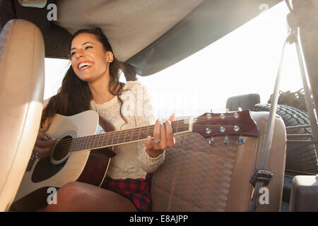 Young woman playing acoustic guitar in back of jeep - Stock Photo