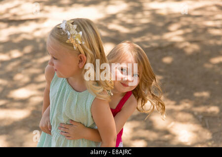 Young girl hiding behind sister in park - Stock Photo