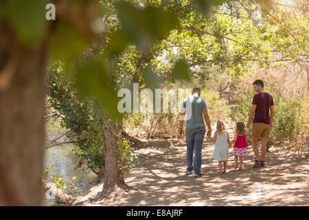 Rear view of male couple strolling with two daughters in park - Stock Photo
