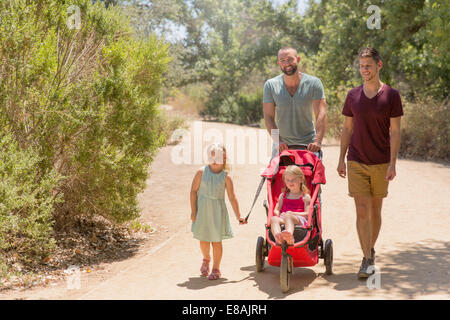 Male couple strolling with two daughters in park - Stock Photo