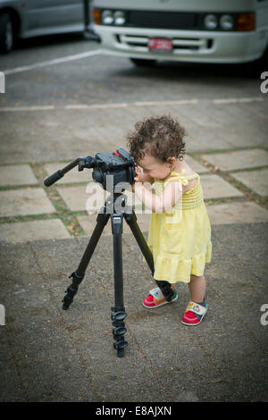 Cute baby girl playing with a tripod - Stock Photo