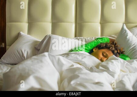 Boy lying asleep in bed - Stock Photo
