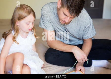 Young man and daughter threading picture book in sitting room - Stock Photo
