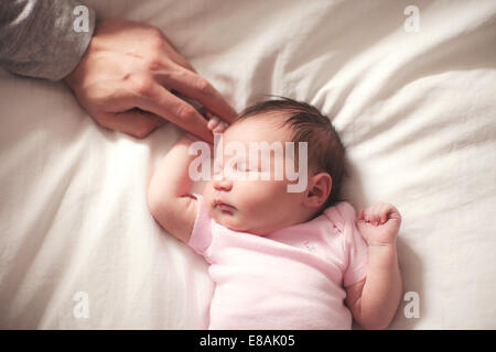 Baby girl sleeping, hands held by father - Stock Photo