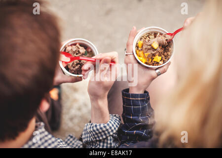 Couple eating tubs of frozen yoghurt treat - Stock Photo