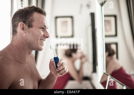 Young couple brushing teeth in his and hers bathroom - Stock Photo