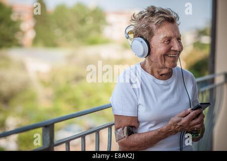 A very senior woman listening to music on headphones on apartment balcony - Stock Photo