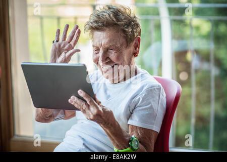 A very senior woman using digital tablet on apartment balcony - Stock Photo