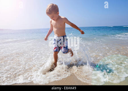 Boy playing on beach, Laguna Beach, California, US - Stock Photo